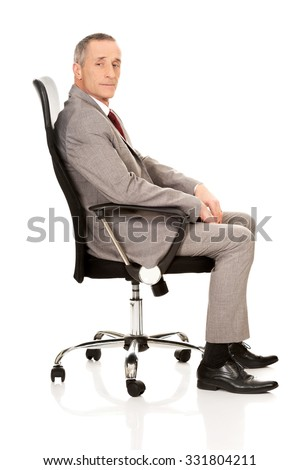 Side view of businessman sitting on armchair. - stock photo