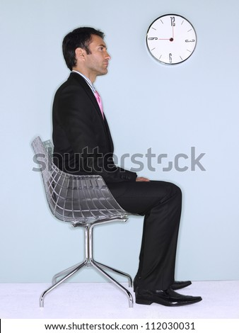 Side view of businessman sitting on chair with wall clock in background - stock photo