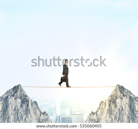 Side view of businessman with briefcase walking in rope between two cliffs on city and sky background. Risk balancing concept
