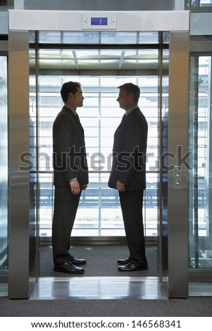 Side view of businessmen standing face to face in elevator - stock photo