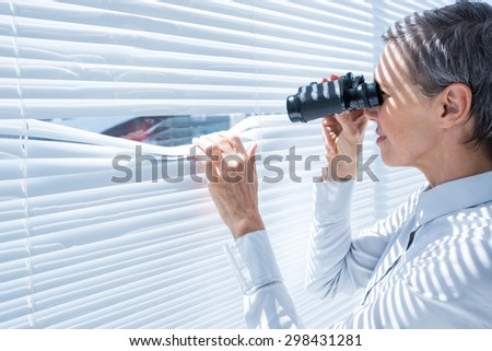 Side view of businesswoman looking through binoculars in the office - stock photo