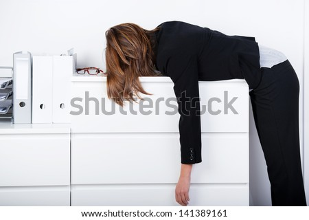 Side view of businesswoman sleeping on counter in office - stock photo