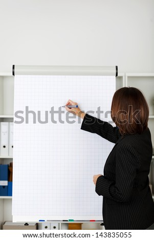 Side view of businesswoman writing on flipchart at office - stock photo