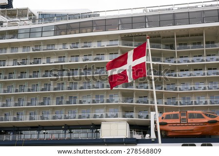 Side view of cabins on cruise liner and Danish flag in Fredericia.  - stock photo