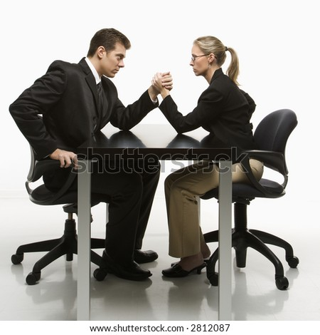 Side view of Caucasian mid-adult businessman and businesswoman arm wrestling on table. - stock photo