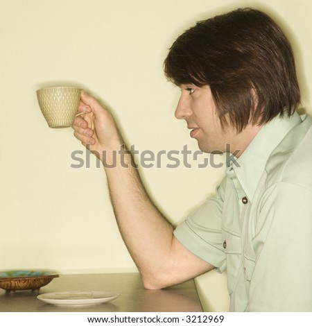 Side view of Caucasian mid-adult man holding up coffee cup. - stock photo