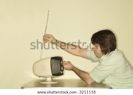 Side view of Caucasian mid-adult man sitting at 50's retro dinette set adjusting old television antenna. - stock photo
