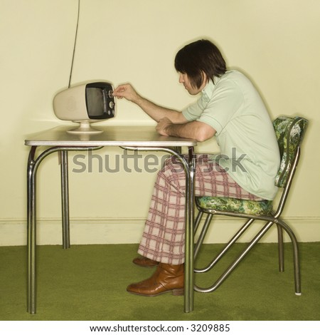 Side view of Caucasian mid-adult man sitting at 50's retro dinette set turning old television knob. - stock photo