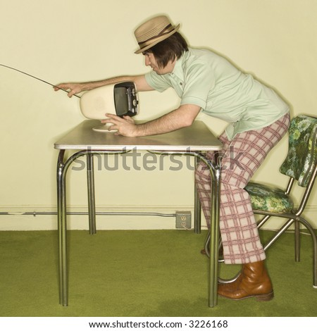 Side view of Caucasian mid-adult man wearing hat and plaid pants leaning over 50's retro dinette set adjusting old television set. - stock photo