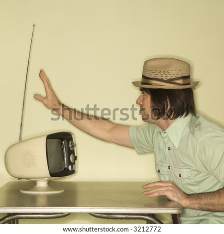 Side view of Caucasian mid-adult man wearing hat sitting at 50's retro dinette set adjusting old television antenna. - stock photo
