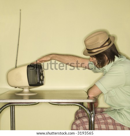 Side view of Caucasian mid-adult man wearing hat sitting at 50's retro dinette set tapping old television set. - stock photo