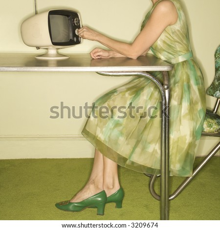 Side view of Caucasian mid-adult woman wearing green vintage dress sitting at 50's retro dinette set turning old televsion knob. - stock photo