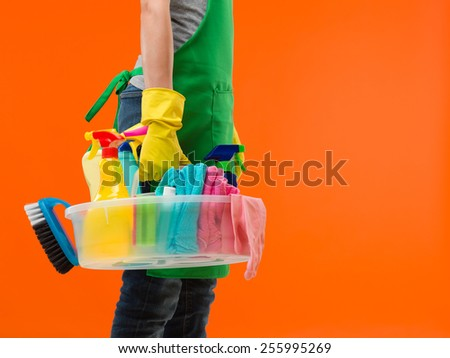 side view of caucasian woman standing and holding cleaning supplies, getting ready for work - stock photo