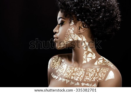 Side view of charming african girl, with black curly hair and patterns of golden foil on her skin, posing on the black background, in studio, close up - stock photo