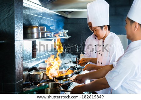 Side view of chefs cooking together - stock photo