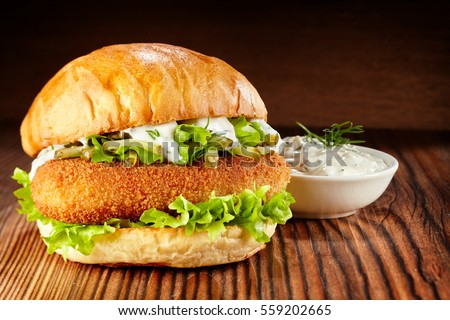 Side view of chicken burger with lettuce and mayonnaise dip on wooden table