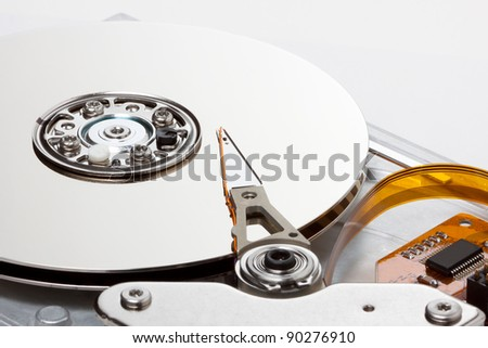 side view of chrome hard drive with a white background; orange communications ribbon and board adds nice contrast to the hard drive - stock photo