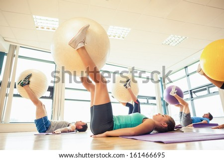 Side view of class exercising with fitness balls at a bright gym - stock photo