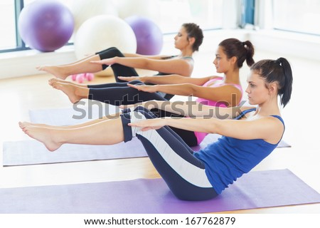 Side view of class stretching on mats at yoga class in fitness studio - stock photo