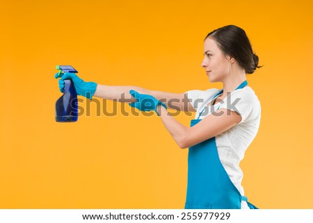 side view of cleaning woman pointing spray with liquid detergent, shooting, against yellow background - stock photo