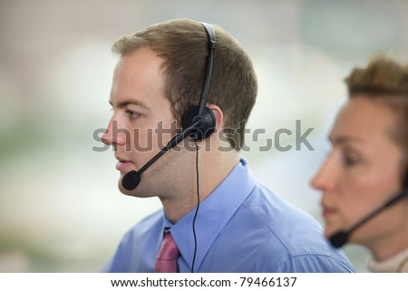 Side view of co-workers wearing headsets. - stock photo