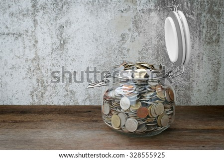 side view of coins in glass bottle on wooden background, thai baht