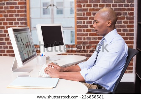Side view of concentrated male photo editor using computer in the office - stock photo