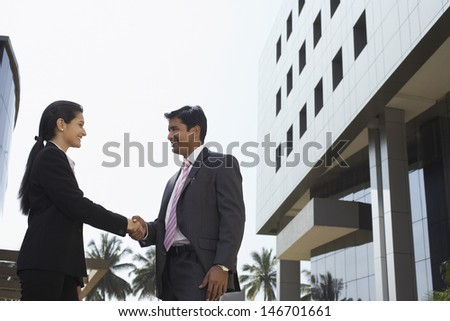 Side view of confident businesswoman and businessman shaking hands outdoors - stock photo