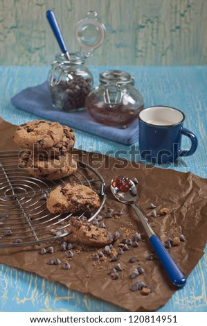 Side view of cookies with chocolate drops on round iron stand and brown paper,cup of milk,  jars with jam and chocolate on cracked blue background - stock photo