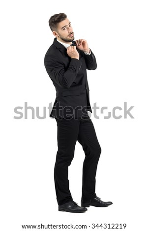 Side view of cool elegant young male model adjusting bow tie looking at camera. Full body length portrait isolated over white studio background. - stock photo