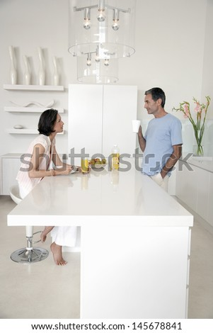 Side view of couple having breakfast at kitchen bench - stock photo