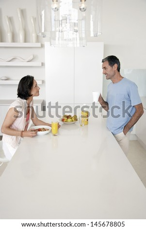 Side view of couple having breakfast in kitchen