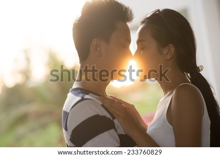 Side view of couple kissing while on the background of declining sun - stock photo
