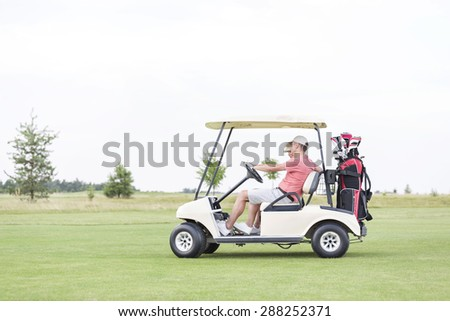 Side view of couple sitting in golf cart against clear sky - stock photo