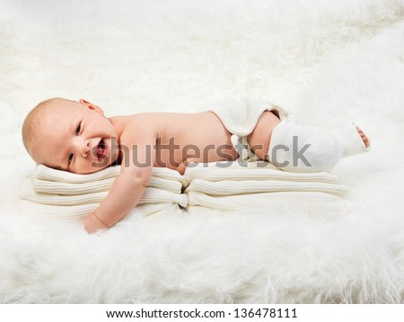 Side view of cute baby boy relaxing on stack of towels