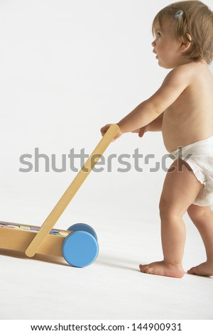 Side view of cute baby girl pushing cart isolated on white background - stock photo