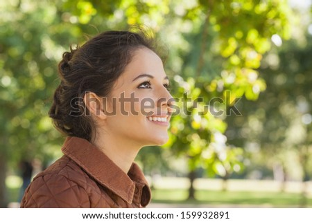 Side view of cute brunette woman wearing a brown coat being in a park - stock photo