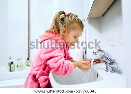 Side view of cute little girl with ponytail in pink bathrobe washing her hands. Copyspace.