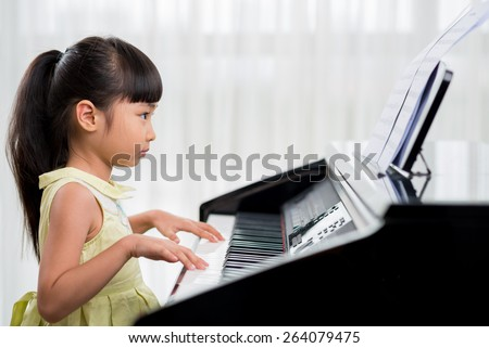Side view of cute Vietnamese girl playing piano - stock photo
