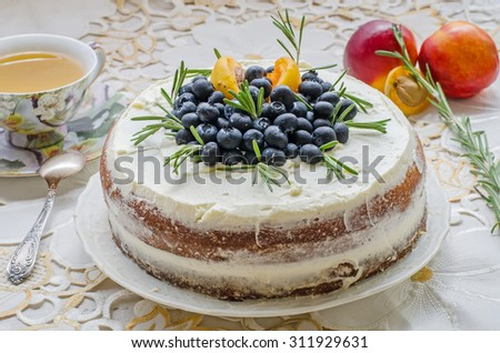 side view of delicious home made cake with cream, berries, rosemary and peach on top on a decorative white table cloth next to a vintage cup of green tea and nectarines - stock photo