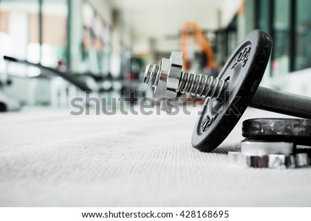 Side view of dumbbell exercise weights on the floor at fitness gym with copy space. Exercise concept. - stock photo
