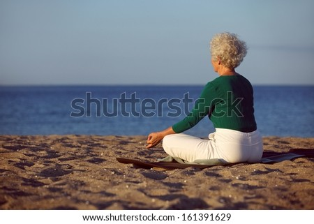 Side view of elderly woman in meditation on the beach. Senior lady sitting on the beach in lotus pose doing relaxation exercise. Old woman doing yoga. - stock photo