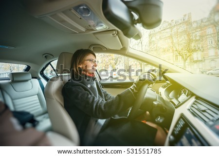 Side view of elegant woman driving confident a car in city enjoying the traffic and good radio station music