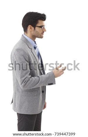 Side view of elegant young businessman turning to left, gesturing, talking.
