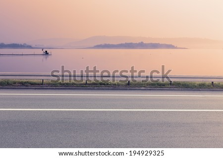 Side view of empty asphalt road and lake at sunrise - stock photo