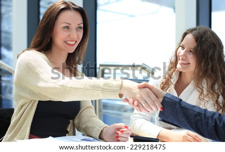 Side view of executives shaking hands during a business meeting in the office  - stock photo