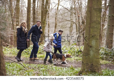 Side view of family walking pet dog in a wood, closer in