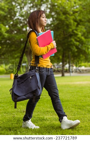 Side view of female college student with books walking in the park - stock photo