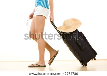Side view of female holidaymaker in flip flops pulling suitcase with sun hat on top, white background.