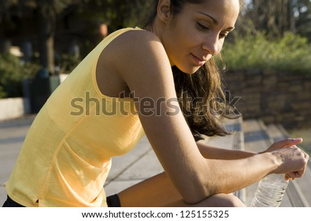 Side view of female jogger sitting with a bottle of water